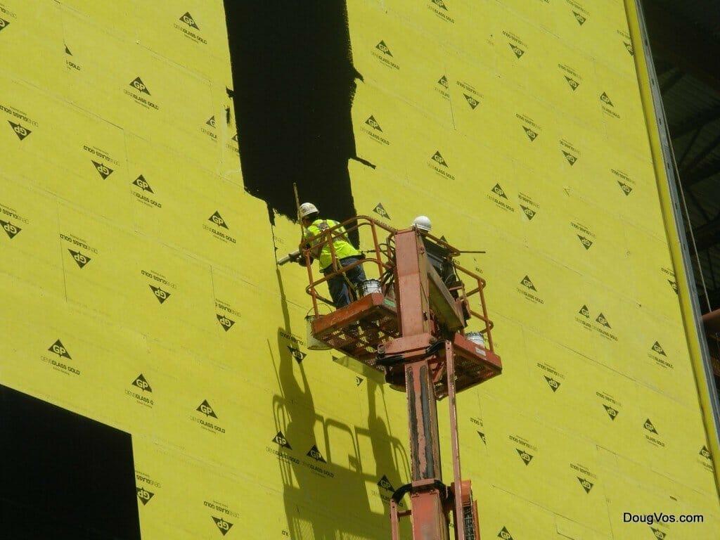 Warning: Casino Under Construction - Black tar sealer on yellow wall board