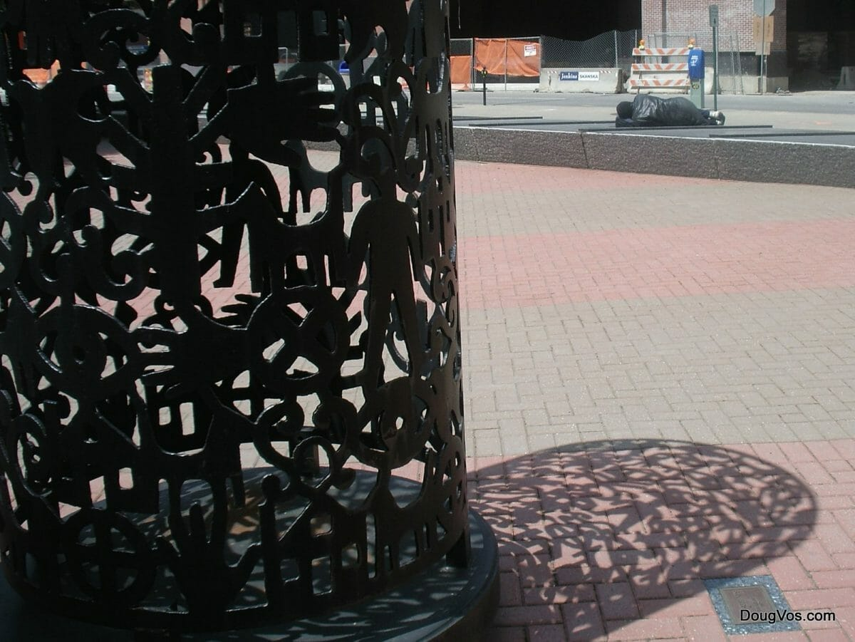 Foreground: Iron hands sculpture in downtown Detroit. Background: Street person is sleeping on some iron grates.