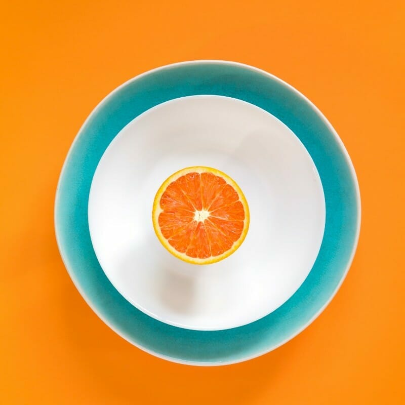 A single sliced orange in a blue and while bowl.
