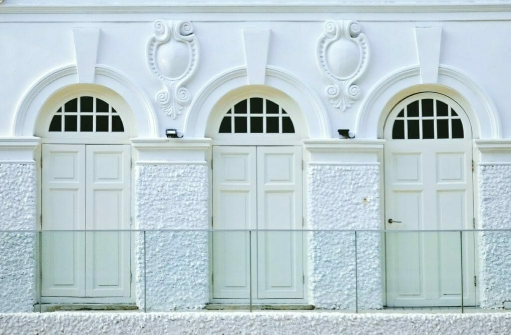 Architectural motif - 3 doors with rounded arch windows with a large keystone across the top of each door.