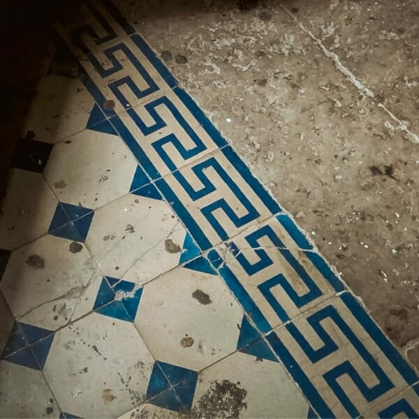 Blue and white floor tiles with meander motif on the border.