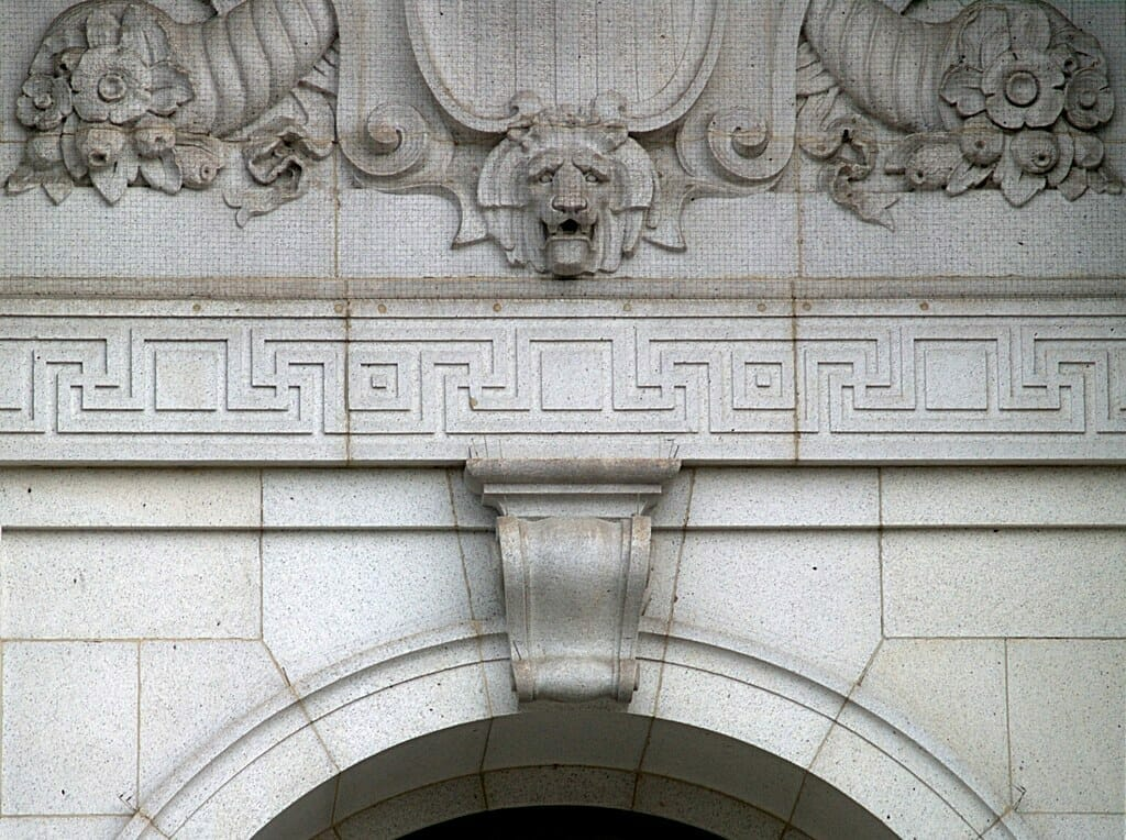 Architectural example photo - lion head surrounded by flowers and cornucopia above meandering stone carving, atop large carved keystone motif in archway.
