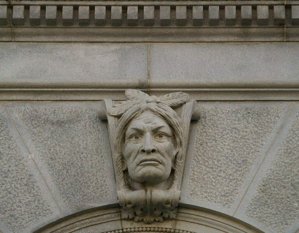 An Indian head carved on keystone - sits on top of arch made of stone.
