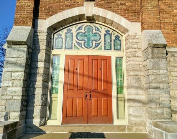 Keystone archway above stained glass windows and double doors at Good Shepherd United Methodist Church in Dearborn, MIchigan.
